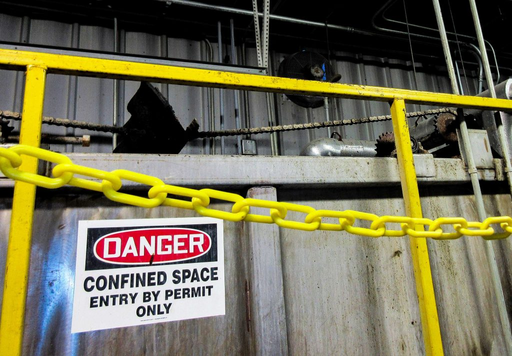 yellow railing with confined space safety sign